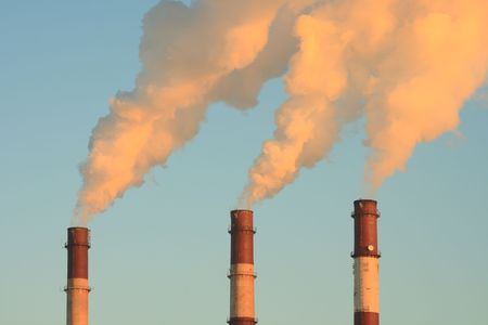 ecological problem: Three smoking chimneys lit by setting sun, against clear sky
