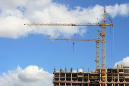 Two yellow cranes on construction site against cloudy sky