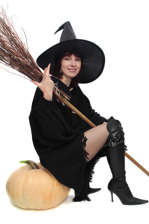 Pretty witch sitting on large pumpkin and holding broom