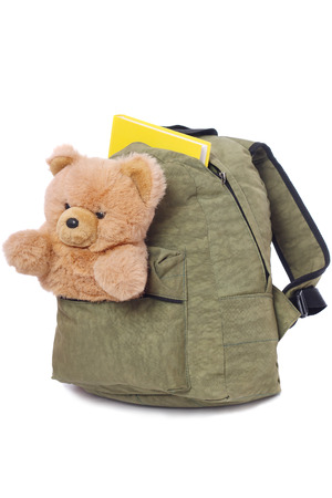 Packaged schoolbag with book and teddy bear in pocket, isolated on white background Stock Photo