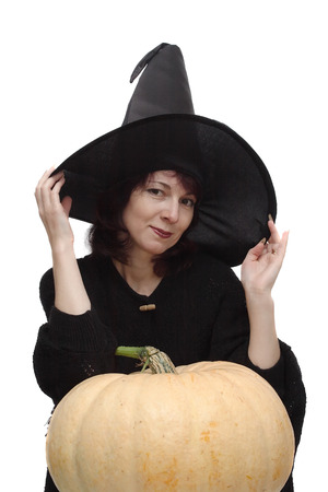 large pumpkin: Pretty witch in black hat, posing leant on a large pumpkin