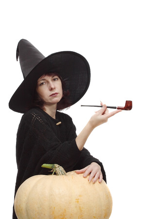 large pumpkin: Pretty witch dressed in black, leant on a large pumpkin, posing with a pipe Stock Photo