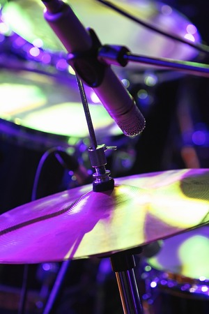 Rock concert series: drum set with microphone, lit by purple and green Stock Photo