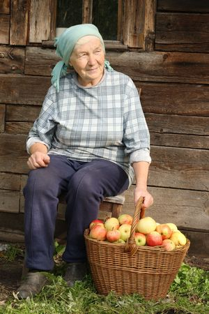 basketful: Senior countrywoman sitting against wooden wall with basketful of apples at her feet