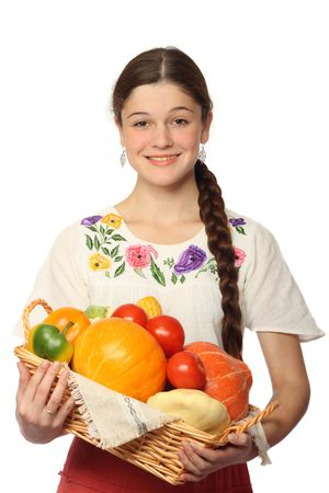 basketful: Young Caucasian girl holding basketful of vegetables, isolated on white background