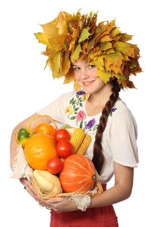Young Caucasian girl in wreath of leaves, holding basketful of vegetables, isolated on white background