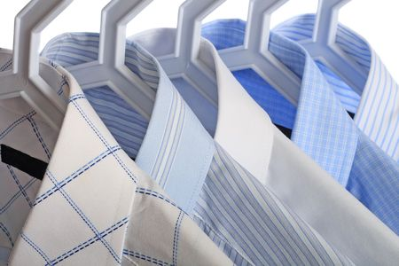 Close-up of five white-and-blue shirts on hangers