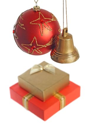 Christmas concept: hanging ball, bell and two gift boxes, isolated on white background, shallow DOF photo