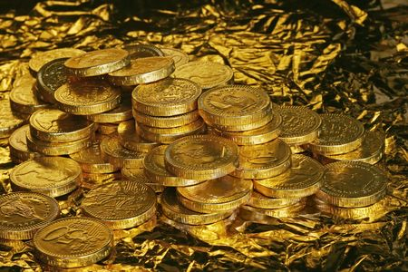 Pile of golden chocolate coins on golden background