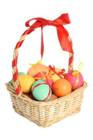 Colored easter eggs in basket, isolated on white background Stock Photo