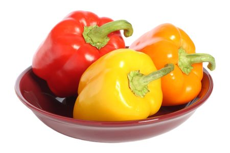 Red, yellow and orange bell peppers on plate, isolated on white background photo