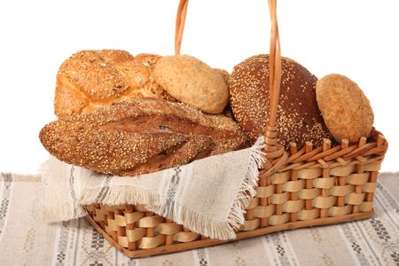 Assorted bread in basket on linen, isolated on white background photo
