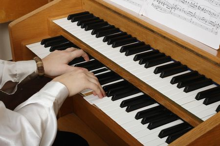 Playing pipe organ. Manual and musicians hands