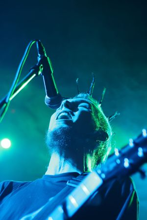 Rock concert: singing man with guitar, in green and blue lighting Stock Photo
