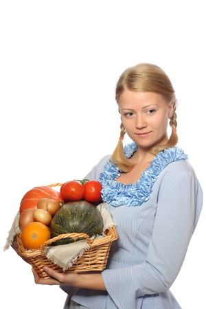 basketful: Young girl in blue dress with basketful of vegetables, isolated on white background Stock Photo