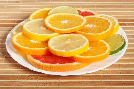plateful: Plateful of citrus slices, on bamboo mat