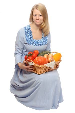 basketful: Sitting girl in blue dress with basketful of vegetables on knees, isolated on white background