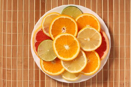 plateful: Plateful of citrus slices on bamboo mat, top view Stock Photo