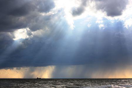 Seascape. The sunrays strike through rainy clouds over gulf Stock Photo - 5576712