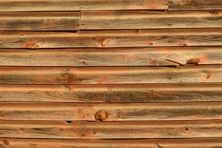 Side of a very old wood house that is decaying and falling apart in fading light Stock Photo