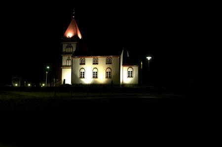 arrives: Icelandic church at night , spotlights as the snow arrives Stock Photo