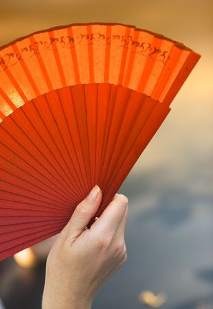 Romantic photo of female hand holding a fan photo
