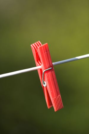 clothepeg: A close up photo of a red clothes-pin