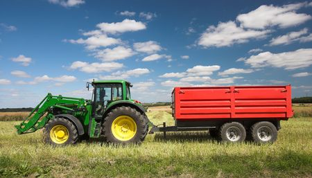 cropland: A photo of a large tractor in harvest time