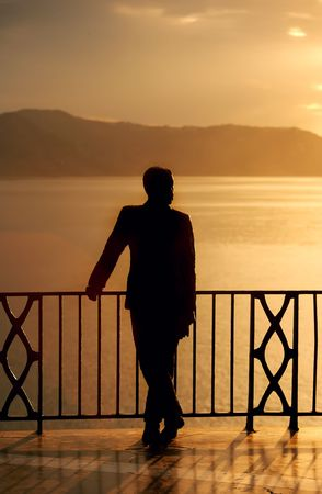 sol: A confident man enjoying the  ocean sunset view from a luxury villa in Spain (Costa Del Sol)