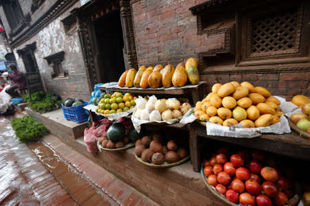 sidewalk sale: Selling fruits on the streets of Kathmandu, Nepal.  Dark and wet, rain season. Stock Photo