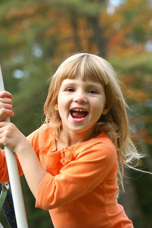 Little girl playing on swing with big smile. photo