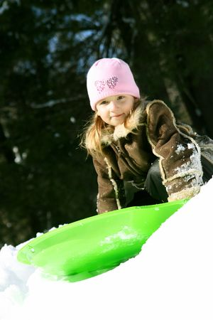 Cute little girl outdoors in winter with green sled photo