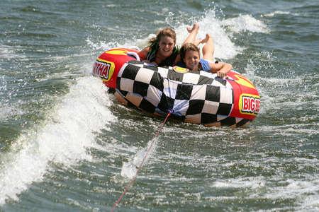 tubing: Teenage girls tubing on lake. Stock Photo