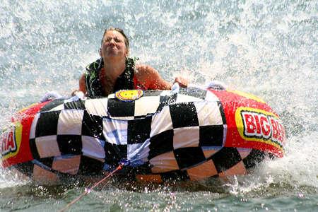 tubing: Teenage girl tubing on lake in summer.