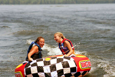 tubing: Two young girls tubing on lake.