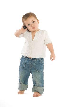 A little boy holding a cellphone near his ear photo