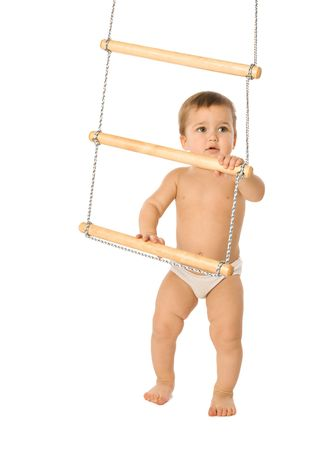 A little boy trying to climb a rope-ladder photo