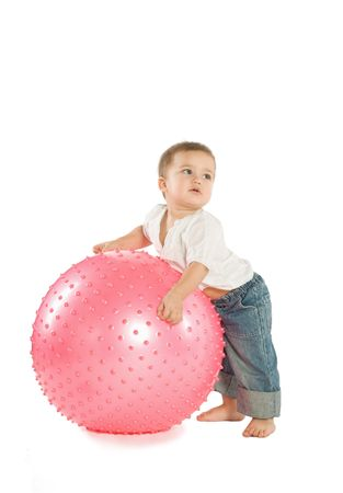 A little boy with a big pink fitness ball