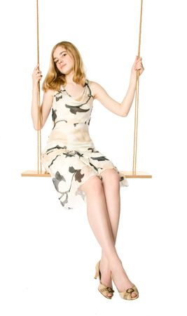 Young blonde sitting on a swing, white background photo