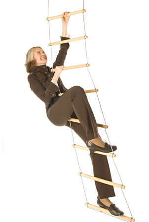 An isolated photo of a businesswoman climbing a rope-ladder photo