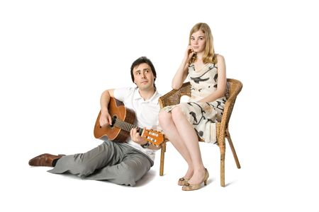 A blond girl and a man playing guitar for her photo