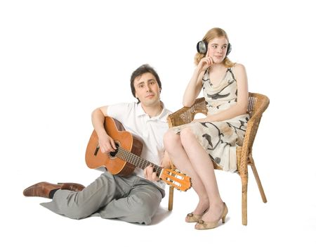 A woman in headphones and a man playing guitar for her photo