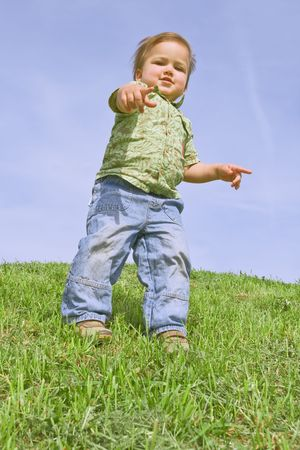 A child pointing at camera, against blue sky photo