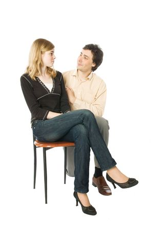kneeled: Young girl sitting on a chair and a man smiling to her