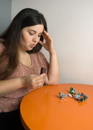 woman contemplating over wrappers of sweets