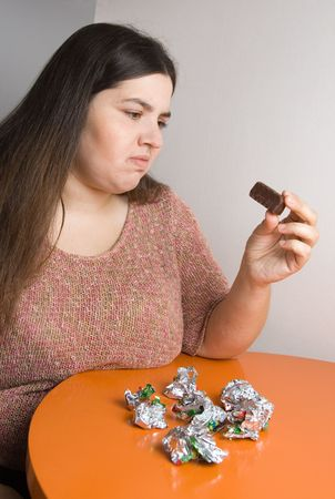 stout: Stout woman contemplating over wrappers of sweets Stock Photo