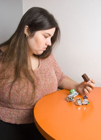 overeating: Stout woman contemplating over wrappers of sweets Stock Photo