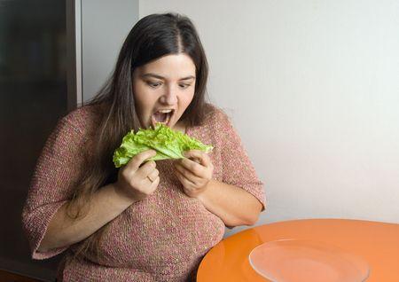 stout: Mujer gruesa tratando de comer una hoja de lechuga Foto de archivo