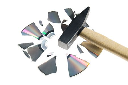 Broken compact disk with a hammer isolated over white  photo