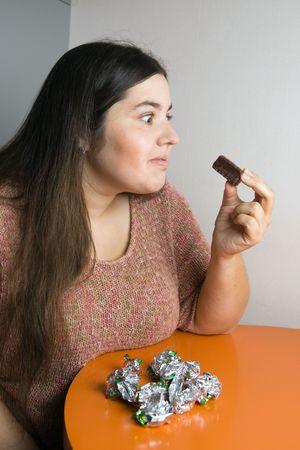 stout: Mujer robusta contemplar m�s de envolturas de dulces Foto de archivo